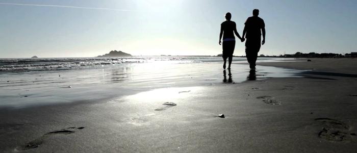 downshifting coppia che si tiene per mano in riva al mare